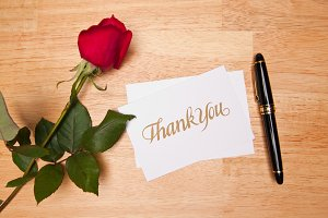 Thank You Card, Pen and Red Rose on a Wood Background.