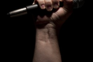 Color Vertical Microphone Clinched Firmly in Male Fist on a Black Background.