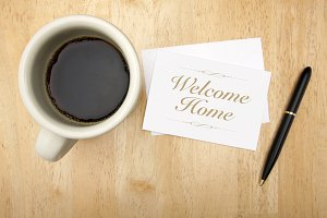 Welcome Home Note Card, Pen and Coffee Cup on Wood Background.