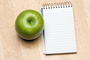 Pad of Paper and Apple on a Wood Background