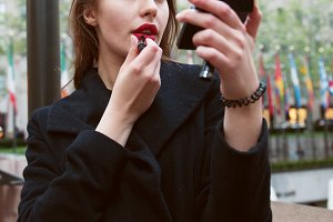 Woman doing red lips makeup