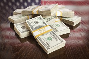 Thousands of Dollars Pile with Reflection of American Flag on Wooden Table.