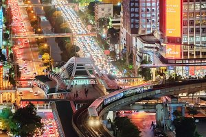 Bangkok City, Thailand -  June26, 2018. Crowd of people crossing the Sathorn intersection bridge with busy streets. Cars traffic on roads and BTS skytrain in transportation concept at night.
