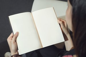 Young girl open the pages of the book empty. text for banner lifestyle and school.