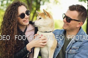 Proud dog owners pretty girl and handsome guy are playing with shiba inu dog, kissing it and scratching its fur relaxing in the park at weekend. People and animals concept.