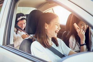 Vacation time and travel, three beautiful young women cheerful travels together for a relaxing holiday. And the laughter in the car.