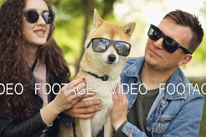 Cute couple handsome guy and his girlfriend are kissing pedigree dog, all wearing sunglasses, people are laughing and touching animal. Pets and owners concept.