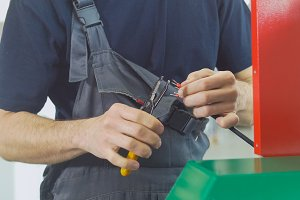 Hands of electrician works with electric wires