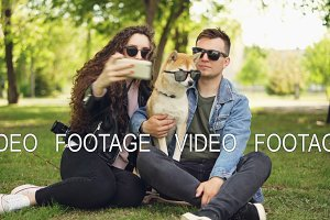 Pretty woman is taking selfie with her boyfriend and adorable dog using smartphone while resting in the park on the grass. Humans and animals are wearing sunglasses.