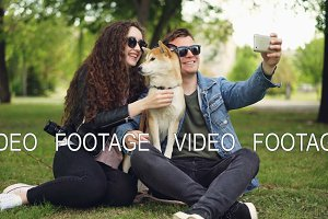 Handsome young man is taking selfie with his pretty wife and cute dog, all wearing sunglasses. Guy is holding smartphone taking pictures and posing.