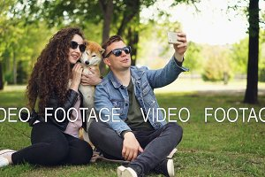 Popular blogger is recording video about himself, his wife and cute dog, man is holding smartphone, talking and looking at camera then on the woman and animal.