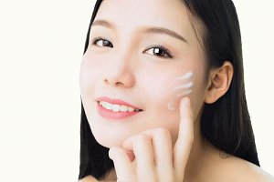 Close up woman is smiling skin beauty and health and apply white cream on face, for spa products and make up. The skin is smooth and beautiful. concept of healthy women.