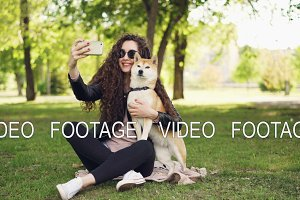 Cheerful blogger pet owner is taking selfie with her dog using smartphone, human and animal are sitting on lawn in the park and posing, woman is caressing and kissing dog.