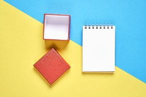 Red gift box,and empty notebook on pastel background, Free space on the notebook for placing text.