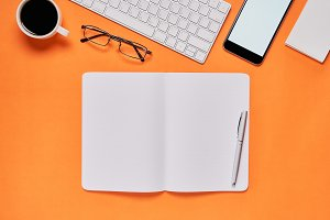 Black screen notebook blank and laptop placed orange background. Suitable for graphics used for advertising.