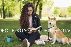 Pretty young lady is reading book in the park and patting cute dog shiba inu breed, well-bred pet is sitting on the grass near its owner. Animals and people concept.