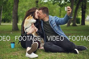 Handsome young man is taking selfie with his girlfriend who is holding pedigree dog, guy is kissing girl then watching photos on screen, people are laughing.