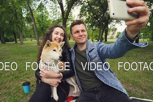 Happy couple is taking selfie in the park kissing and looking at smartphone, while young woman is holding and caressing cute puppy shiba inu breed.