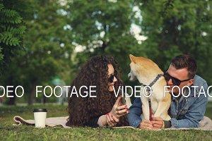 Young woman is showing funny pictures on smartphone to her boyfriend while relaxing in park with pet dog, people are lying on plaid on grass and watching screen.