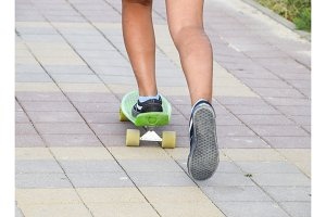 Legs of a teenager riding a skateboard on the sidewalk.