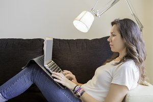 woman using a laptop on a sofa