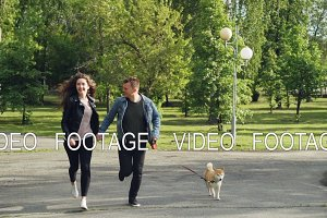 Slow motion of young married couple running in the park with small dog enjoying freedom and activity with beautiful green trees and grass around them.