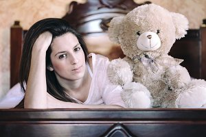 woman lying in bed with her teddy