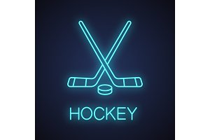 Crossed hockey sticks with puck neon light icon