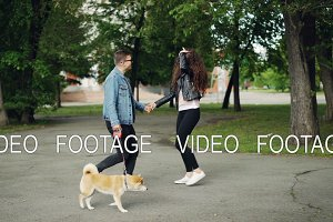 Slow motion of pretty young woman walking in the park with her husband and cute small dog, she is chatting, laughing and playing with animal. Nature and leisure concept.