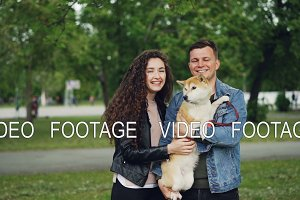 Slow motion portrait of adorable couple and purebred dog standing together in the park, looking at camera and smiling. Nature and family concept.