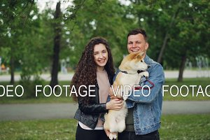 Slow motion portrait of man and woman proud dog owners holding adorable puppy, looking at camera and smiling standing in park on summer day.