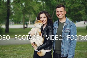 Slow motion portrait of attractive young woman brunette holding her dog standing in the park with boyfriend. Happy people are looking at camera and smiling.