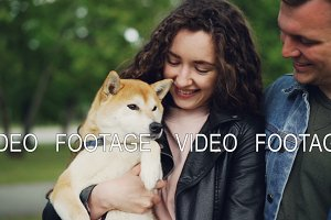 Slow motion of happy couple holding beautiful pedigree dog, looking at it and shaking its paw then touching its nose. Loving owners, glad animals and nature concept.