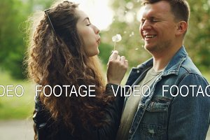 Slow motion of adorable couple having fun in the park, young woman is blowing dandelion blowball in her boyfriend's face, he is laughing and closing eyes.