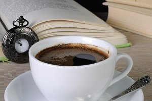 cup of coffee among the books