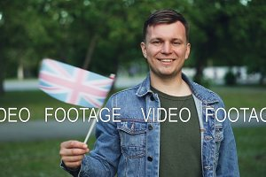 Slow motion portrait of joyful Englishman looking at camera, smiling and waving official flag of the United Kingdom. Travelling around the world and people concept.