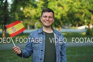 Slow motion portrait of handsome young man with expressive face waving Spanish official flag, smiling and looking at camera. Happy people and national pride concept.