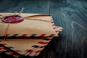 Old letters envelopes with a wax magic stamp triquetra on wooden table