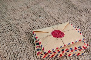 Old letters envelopes with a wax magic stamp triquetra on burlap