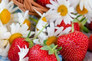 Basket of fresh ripe sweet strawberries with daisies
