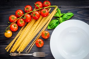 Italian spaghetti, served plate, on a wooden table with bunch tomatoes.