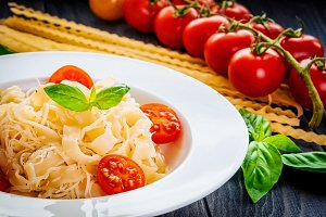 plate of italian pasta with tomatoes, basil and cheese