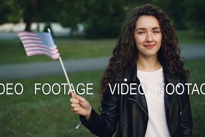 Slow motion portrait of pretty girl happy American student waving US flag, looking at camera, smiling and laughing. Patriotic youth, counties and nationalities concept.