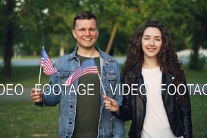 Slow motion portrait of happy American couple waving US flags standing in the park together, looking at camera and smiling. Relationship, people and countries concept.