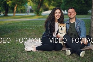 Slow motion portrait of adorable couple and pedigree dog sitting on blanket on grass in the park, looking at camera and smiling. Nature and family concept.