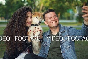 Slow motion of handsome guy taking selfie with his wife and dog in the park, cheerful man is posing while pretty woman with curly hair is hugging shiba inu puppy.