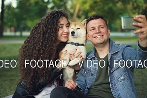 Slow motion of happy pair girl and guy taking selfie with cute dog posing and kissing animal holding smartphone. Modern technology, parks and leisure concept.