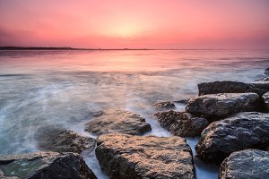 Sunrise from the sea with rocks