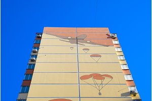 A multi-storey house with a painted wall. Figure depicting the landing of paratroopers from an airplane