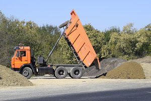 The dump truck unloads rubble. The truck dumped the cargo. Sand and gravel. Construction of roads